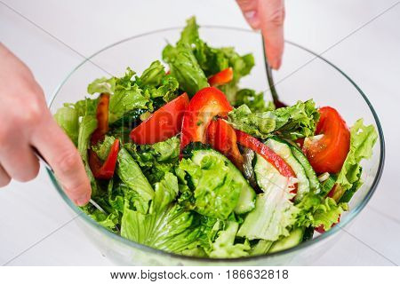 Healthy eating, vegetarian food, dieting and people concept - close up of young woman dressing vegetable salad with olive oil on a white background