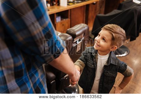 Nice to meet you. Nice cute joyful boy smiling and looking at his barber while greeting him