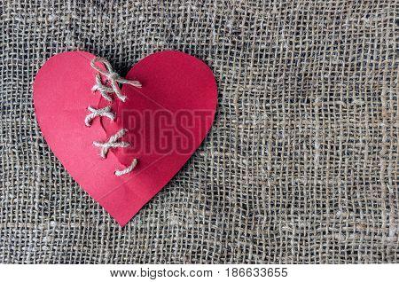 A broken red heart. Sewn thread. The concept of divorce separation quarrel.
