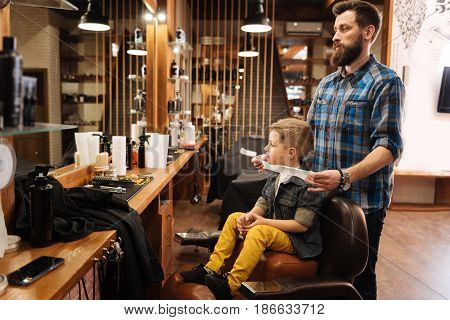 I want a modern haircut. Nice cute young boy visiting a barbershop and getting his hair cut while wanting to look stylish