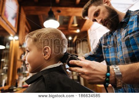 Cutting hair. Nice bearded male hairdresser holding a hair cutting machine and cutting his clients hair while standing behind him