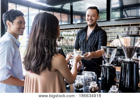 Cheerful bartender serving coffee over the bar counter to a young female customer standing next to her boyfriend in the cafeteria