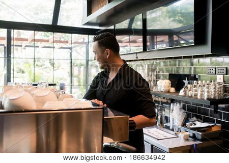 Young man smiling while working as barista behind the bar counter of a clean and modern coffee shop