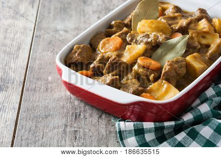 Beef meat stewed with potatoes, carrots and spices in ceramic pot on wooden table