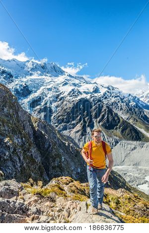 Hiking hiker man tramping in New Zealand mountains. Alpine trekking lifestyle mountaineering excursion with snow capped mountains landscape.