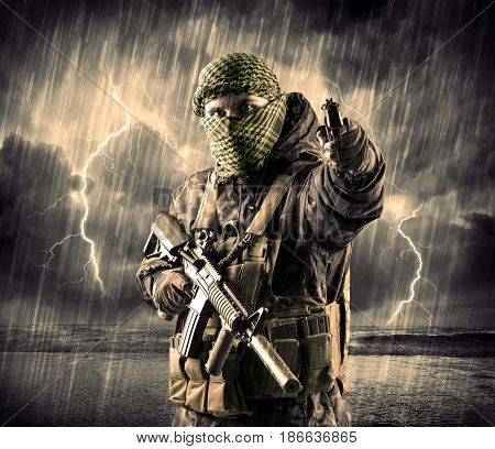 Portrait of a dangerous armed terrorist with mask and gun in a thunderstorm with lightning