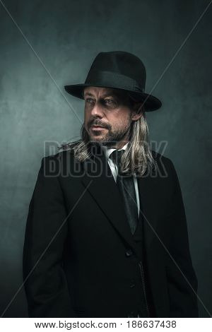 Retro Victorian Style Man With Blond Long Hair And Hat. Wearing Black Suit And Tie.