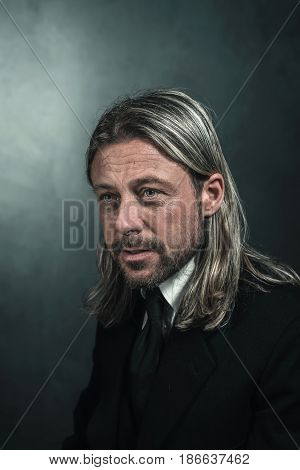 Retro Victorian Style Man With Blond Long Hair And Beard. Wearing Black Suit And Tie.