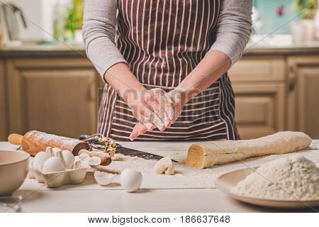 Woman bake pies. Confectioner makes desserts. Making buns. Dough on the table. Knead the dough. A woman in a striped apron is cooking in the kitchen