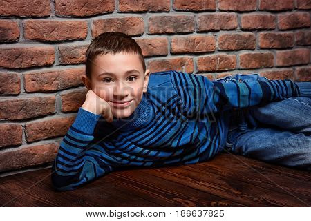 Portrait of a smiling nine year old boy leaning against the brick wall.