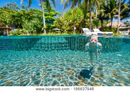 Split underwater photo of adorable little girl diving and swimming in pool on summer vacation