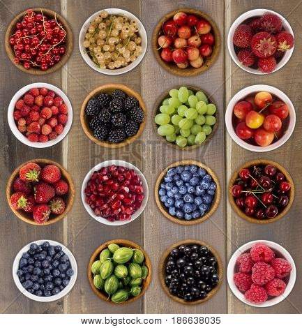 Collage of fruits and berries. Blueberries blackberries cherries grapes strawberries currants raspberries wild strawberries bilberries gooseberries and pomegranate. Collection of fruits and berries in a bowl. Top view.