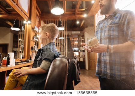 Modern barbershop. Nice male pleasant barber standing in the barbershop and holding a special brush while working with his client