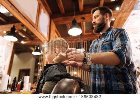 Absolute professional. Nice bearded male hairdresser standing behind his client and doing his job while working in the barbershop
