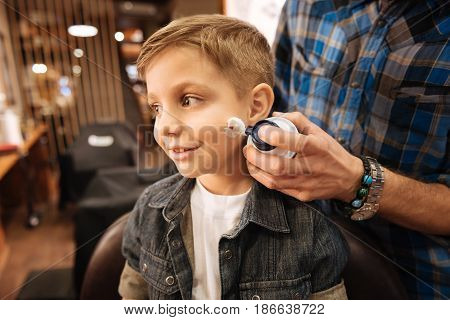 First shaving. Nice pleasant male barber holding a shaving foam and using it while preparing to shave his young client