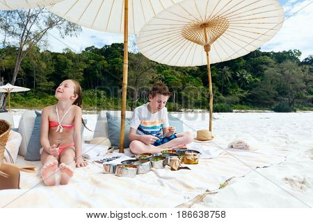 Kids brother and sister on a tropical beach having picnic