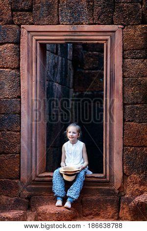 Little girl in ancient Banteay Srei temple in Siem Reap, Cambodia