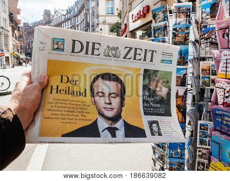 PARIS FRANCE - MAY 15 2017: Man buys German Die Zeit newspaper reporting handover ceremony presidential inauguration of the newly elected French President Emmanuel Macron in Paris France
