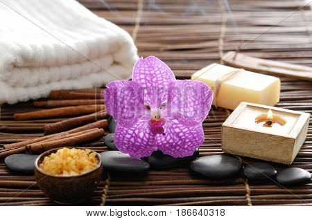 spa setting on mat background with pink orchid, towel,soap