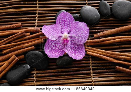 Pile of black stones with pink orchid. cinnamon on mat