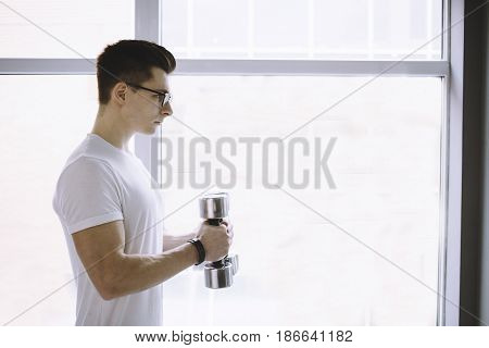 Young attractive sportsman in whit shirt seriously doing exercises with dumbbells standing near big white window. Close up. Profile view