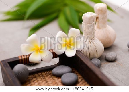 herbal ball ,stones, frangipani ,bamboo leaf on gray background