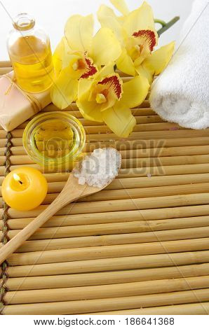 Spa setting with yellow orchid,towel, oil ,salt in spoon,candle with mat texture