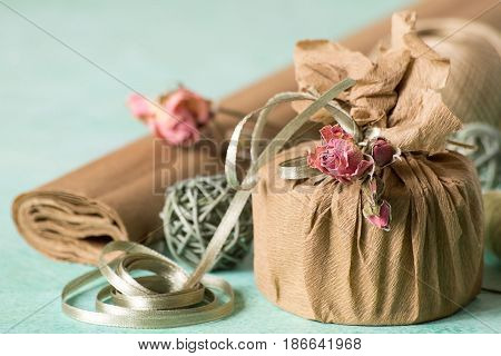 Creativity Packing gifts in vintage style using natural materials. Paper, decorative tape, dried flowers and threads on a light background. Selective focus.