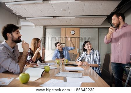 Can I add something. Attractive bearded male person standing in semi position gesticulating while talking to his friends