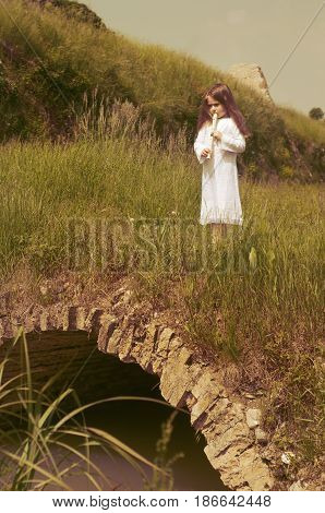 Portrait of little Caucasian girl in white dress with flute stands on little stone bridge outdoor (Palmanova Friuli-Venezia Giulia Italy).
