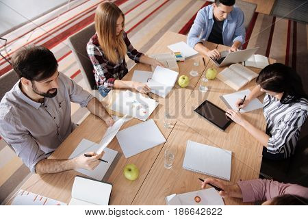 Brain storming. Five people sitting opposite each other doing their tasks while being very attentive