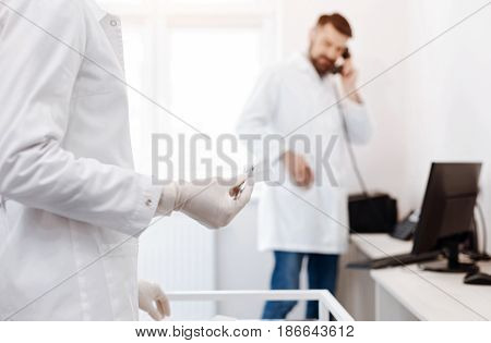 Sterile instrument. Selective focus of scissors with a piece of a bandage being in hands of a plastic surgeon with a doctor making a call in the background