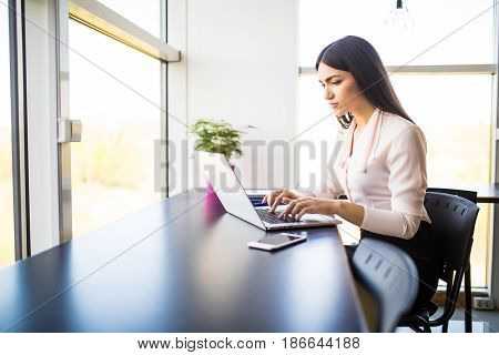 Young Beautiful Woman Using Her Laptop While Sitting In Chair At Her Working Place