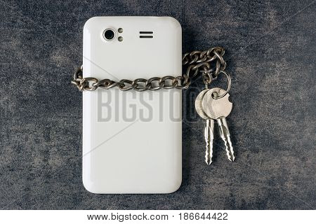 Modern mobile phone and a chain with keys. The concept of information security. Social network forgot password piracy.