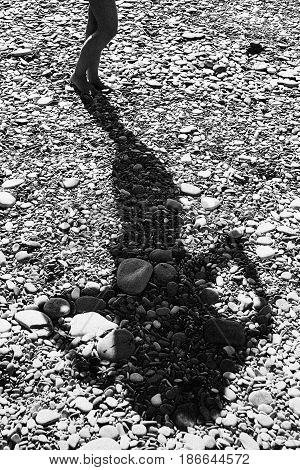 Shadow of a graceful slender girl on stones. Black and white image.