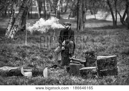 Vape Man. Photo Of A Brutal Bearded Young Man Having Rest After Chop Firewood And Vaping An Electron