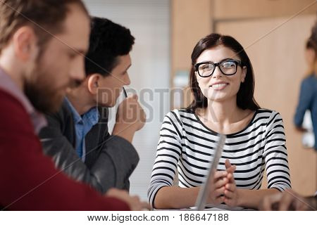 Feel the progress. Beautiful positive female wearing striped cardigan keeping smile on her face while looking straight at camera
