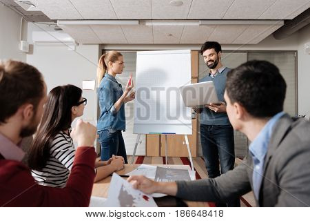Take highlighter. Handsome delighted man holding laptop in both hands keeping smile on face while standing near board