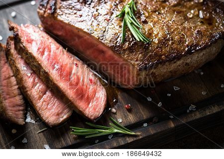 Fresh grilled meat. Grilled beef steak medium rare on wooden cutting board. Close up.