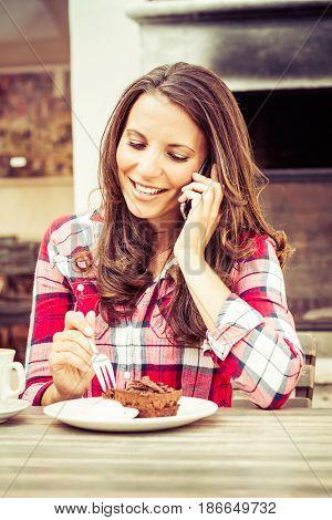 Woman eating cake talking on phone