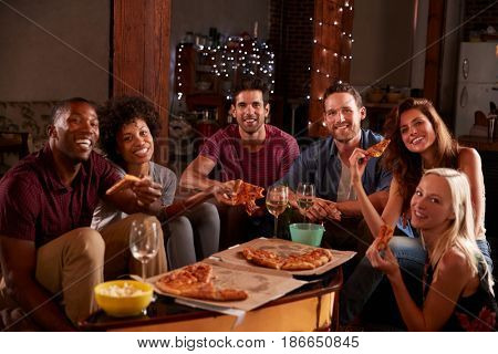 Young adults eating pizza at a party look to camera