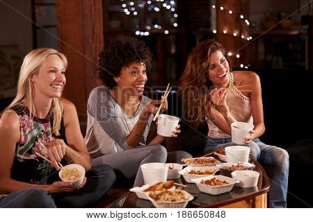 Three female friends eating a Chinese take-away watching TV