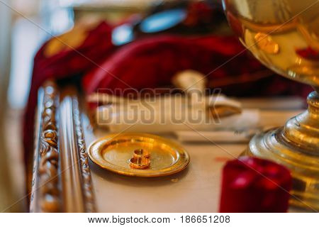 Two golden wedding rings in ceremonial bown on church altar.