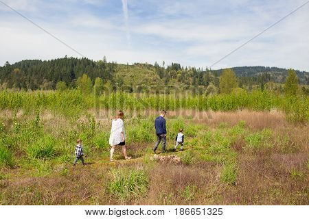 Family walking together across a large natural field on a trail in Oregon.