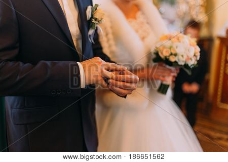 The view of the hands. The groom is purring on the golden wedding ring at the background of the church