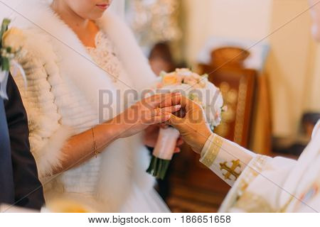 The priest is putting the golden wedding ring on the bride. Close-up view of the hands