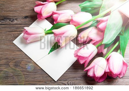 bouquet of pink tulips and postcard on wood
