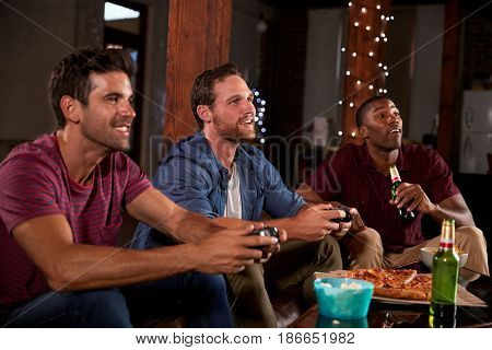 Three male friends playing video games and drinking at home