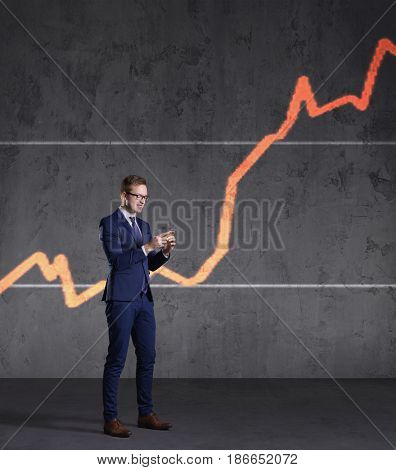 Businessman with smartphone standing on a diagram background. Business, office, success, concept.