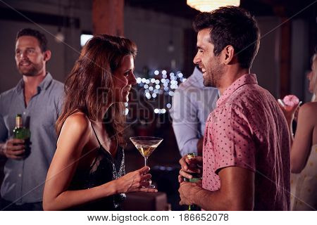 Young man and woman talk and laugh at a party, side view